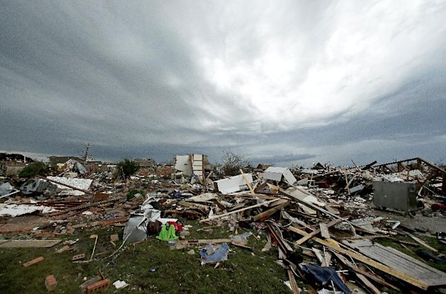 Storm clouds build in the distance beyond tornado-ravaged homes Tuesday, May 21, 2013, in Moore, Okla. A huge tornado roared through the Oklahoma City suburb Monday, flattening entire neighborhoods an