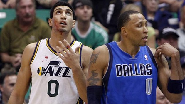 Utah Jazz center Enes Kanter (L) bleeds as he walks past Dallas Mavericks forward Shawn Marion during the first half of their NBA basketball game in Salt Lake City