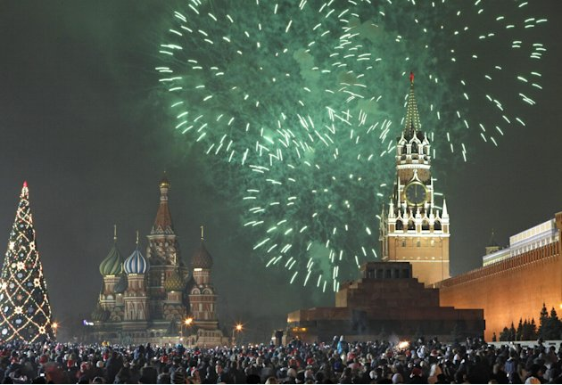 Russians celebrate the New Year on Red Square in Moscow, with the Kremlin in the background, right, and St. Basil's cathedral in background left, Russia, Sunday, Jan. 1, 2012. Tens of thousands of peo