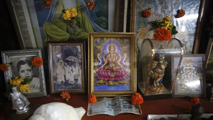An Indian rupee currency note is seen next to the portrait of the Hindu Goddess of wealth Laxmi inside a shop in Mumbai