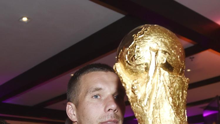 Germany's Lukas Podolski poses with the World Cup trophy during the DFB-WM gala party in Rio de Janeiro