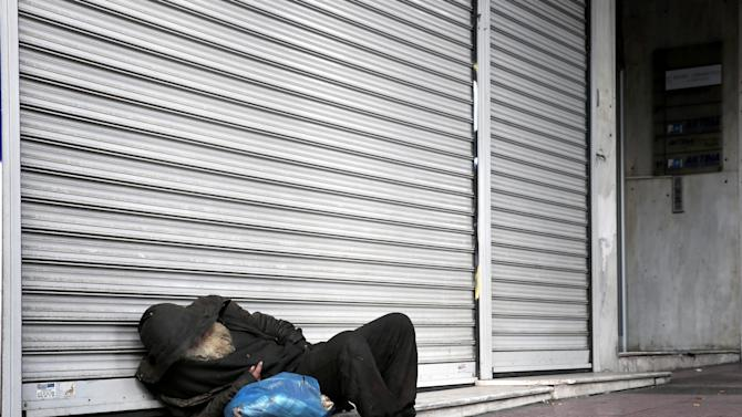 A homeless person sleeps in front shuttered shop due to crisis at the upscale Voukourestiou street in Athens on Wednesday, Nov. 13, 2013. Greece battles a sixth year of recession and high unemployment from austerity measures in exchange for ongoing rescue loans from International Monetary Fund and the other 16 European Union countries that use the euro. (Petros Giannakouris)