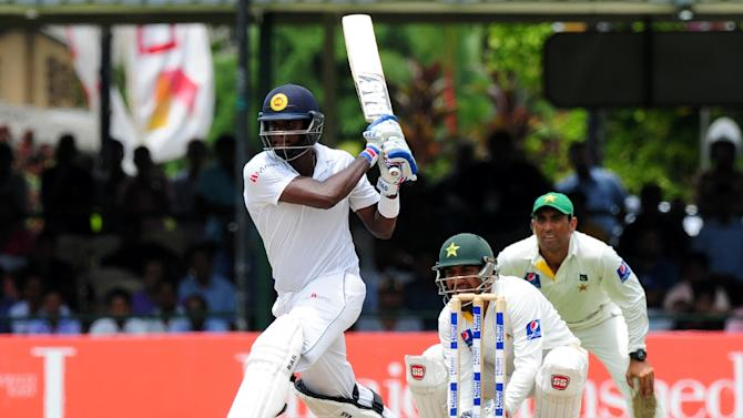 Sri Lanka captain Angelo Mathews (L) plays a shot as Pakistan wicketkeeper Sarfraz Ahmed (C) and fielder Younis Khan (R) look on during the final day of the second Test in Colombo on June 29, 2015