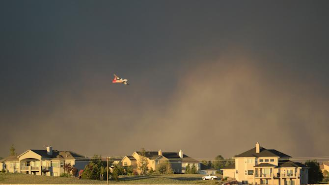 A slurry bomber flies over homes as it prepares to drop fire retardant on the Black Forest Fire in northeast of Colorado Springs on Tuesday, June 11, 2013. The fire consumed an estimated 7500 acres. It damaged 40-60 structures and forced the evacuation of thousands of people. As of Tuesday night the fire was reported as zero percent contained. (AP Photo/BryanOller)