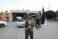 A Free Syrian Army soldier stands at the Bab al-Salam border crossing to Turkey on July 22, 2012. Anatolia reported that rebel fighters took Al-Salam on July 22 after hours of fighting during the night, and that the sounds of the battle could be heard from the Turkish side of the border. (AFP Photo/Adem Altan)