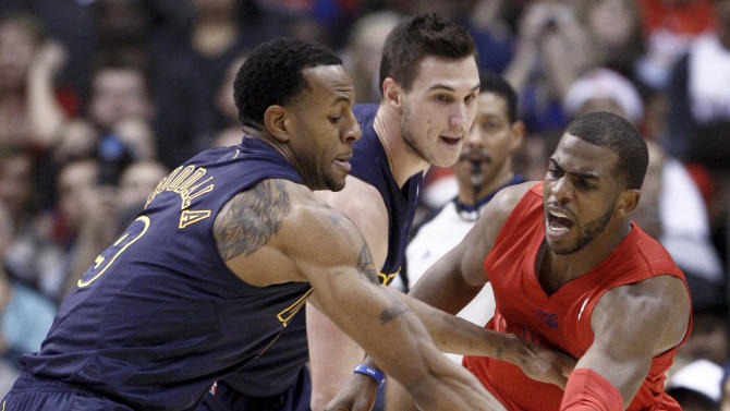 Los Angeles Clippers guard Chris Paul, right, passes the ball under pressure from Denver Nuggets' Andre Iguodala (9) and Danilo Gallinari, center, during the first half of their NBA basketball game, Tuesday, Dec. 25, 2012, in Los Angeles. (AP Photo/Jason Redmond)