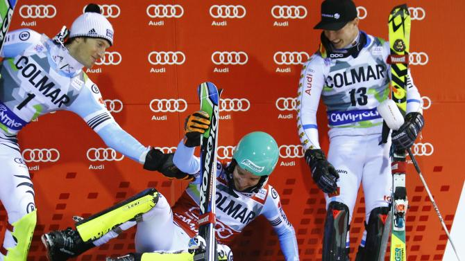 Neureuther of Germany slips on the podium next to second placed compatriot Dopfer and third placed Byggmark of Sweden after winning the men's World Cup Slalom skiing race in Madonna di Campiglio