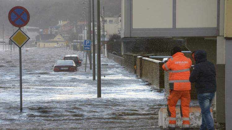 Men watch as cars are surrounded by flood waters in a street in Helsingborg