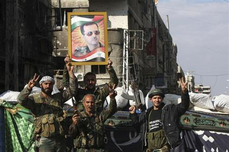Security personnel loyal to Syria's President Bashar al-Assad flash the 'V' signs in Hujaira town, south of Damascus