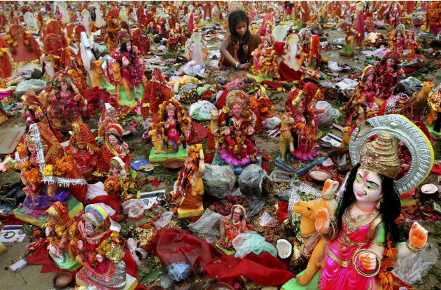 An Indian girl looks for reusable material amid idols of Hindu Goddess Dashama on the banks of River Sabarmati in Ahmedabad, India, Tuesday, Aug. 9, 2011. The ten-day long Dashama festival that culmin
