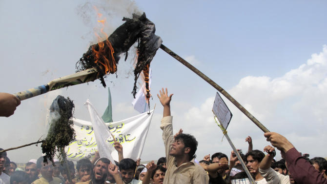 """Afghans burn an effigy of U.S. President Barack Obama during a protest in Khost, south-east of Kabul, Afghanistan, Saturday, Sept. 15, 2012. A few hundred of university students protested against an anti-Islam film which depicts the Prophet Muhammad as a fraud, a womanizer and a madman, in Khost, shouting """"death to America.""""(AP Photo/Nashanuddin Khan)"""