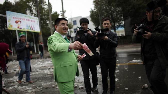 Chinese multimillionaire Chen Guangbiao gives money away to street cleaners during an event organized by him in Nanjing