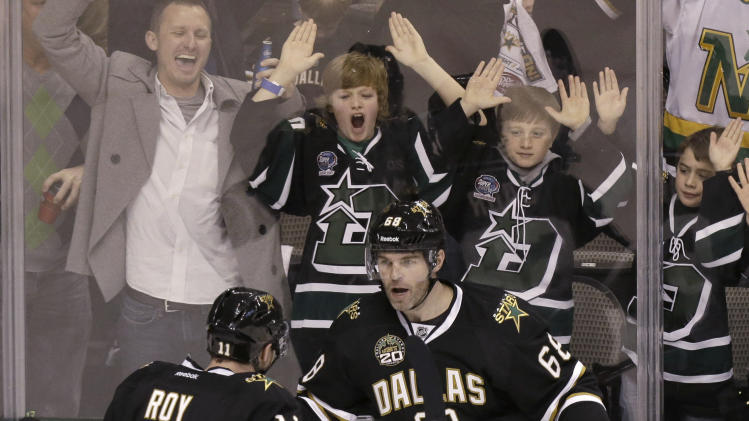 Fans cheers in the background as Dallas Stars right wing Jaromir Jagr (68) celebrates his goal with teammate Derek Roy during the first period of an NHL hockey game against the Phoenix Coyotes on Saturday, Jan. 19, 2013, in Dallas.  (AP Photo/LM Otero)