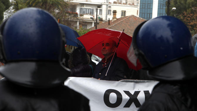 An employee of Laiki bank holding  an umbrella is seen behind riot police during a rally outside of the parliament in capital Nicosia, Cyprus, Friday, March 22, 2013. Cypriot authorities were putting the final touches Friday to a plan they hope will convince international lenders to provide the money the country urgently needs to avoid bankruptcy within days. (AP Photo/Petros Karadjias)