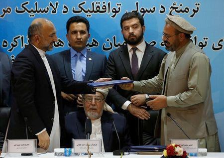 Signing peace deal, Afghan warlord calls for an 'end to current crisis'