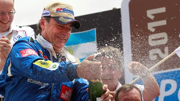 Third placed Carlos Sainz of Spain (L) sprays champagne during the podium ceremony of the third South American edition of the Dakar Rally 2011, in Buenos