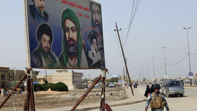 "In this Sunday, Feb. 24, 2013 photo, an Iraqi policeman walks past a sign showing Shiite religious leaders and Shiite's who were killed during a fight between US troops and al-Mahdi Army militia in the Jihad neighborhood of west Baghdad, Iraq. The fliers claiming to be from a new Iranian-linked Shiite militant group began turning up last week in front of Iraqi Sunni households bearing a chilling message: Get out now or face ""great agony"" soon.   (AP Photo/ Karim Kadim)"
