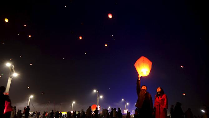 People release paper lanterns to pray for good fortune in the beginning of the Chinese Lunar New Year, at a square in Puyang