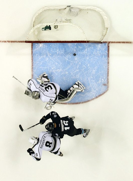 Los Angeles Kings goalie Jonathan Quick (32) is scored on by San Jose Sharks defenseman Dan Boyle (22) (not seen) as San Jose Sharks center Joe Thornton (19) and Los Angeles Kings defenseman Drew Doug