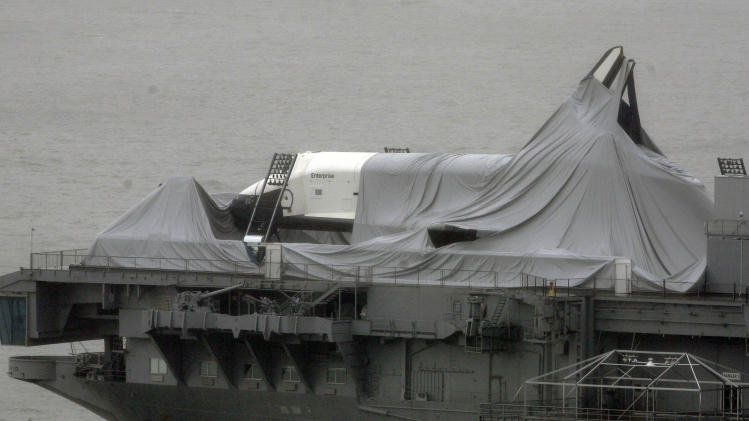 FILE - In this Tuesday, Oct. 30, 2012, photo,  the space shuttle Enterprise is draped with cloth on the deck of  the Intrepid Sea, Air & Space Museum, at its dock on the Hudson River in New York.  NASA spokeswoman Lisa Malone said Friday, Nov. 2, 2012,  officials with the Intrepid Sea, Air and Space Museum told the space agency the Enterprise suffered minor damage during Superstorm Sandy which struck on Monday.  (AP Photo/Peter Morgan, File)