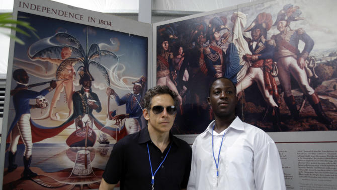 Backdropped by images of Haiti's independence from France, U.S. actor and comedian Ben Stiller poses for a photo with an unidentified man at the Caracol Industrial Park, in Caracol, Haiti, Monday, Oct. 22, 2012.  The Haitian government will host Hillary and Bill Clinton, a delegation of foreign investors and a crowd of celebrities including Stiller, Sean Penn and Donna Karan, Monday, to showcase the marquee project of the U.S. aid effort since the 2010 earthquake. The Clintons and their allies hope the $300 million facility will transform the northern part of this impoverished country by providing thousands of desperately needed jobs. (AP Photo/Dieu Nalio Chery)