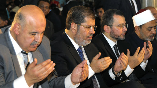 Egyptian Vice President, Mahmoud Mekki, left, President Mohammed Morsi, second left, Prime Minister Hesham Kandil, third left, and the Grand Sheik of Al-Azhar, Ahmed el-Tayeb, right, attend Eid al-Fitr prayers in Amr Ibn Al-As mosque to mark the start of a three-day Muslim holiday that marks the end of the Muslim holy month of Ramadan on Sunday, Aug. 19, 2012. In his sermon, the imam, Ismail el-Diftar, not seen,  prayed for martyrs and the liberation of Jerusalem's al-Aqsa mosque. (AP Photo/Egyptian Presidency)