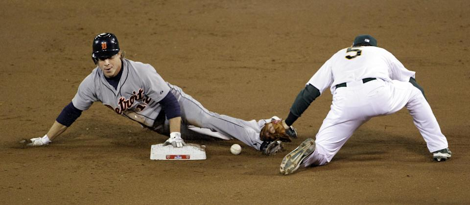 Detroit Tigers Andy Dirks is safe at second on a steal after the ball gets away from Oakland Athletics shortstop Stephen Drew (5) in the second inning of Game 5 of an American League division baseball series in Oakland, Calif., Thursday, Oct. 11, 2012. (AP Photo/Eric Risberg)