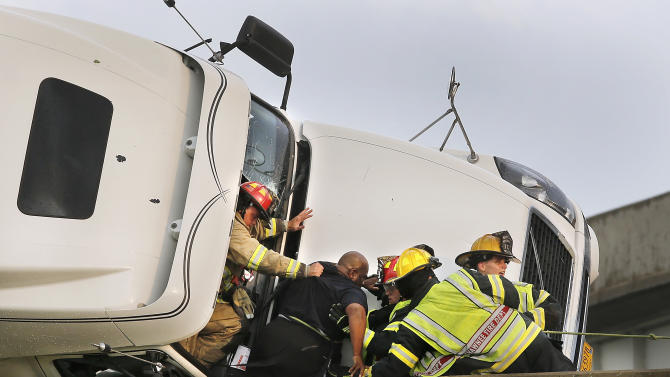 Shawnee firefighters assist driver Marco Corr as he is taken from the cab of his overturned truck, in Shawnee, Okla., Sunday, May 19,  2013. Corr was taken out of the cab through the front windshield. A tornado caused extensive damage along Interstate 40 at the junction with U.S. 177.  (AP Photo/The Oklahoman, Jim Beckel)