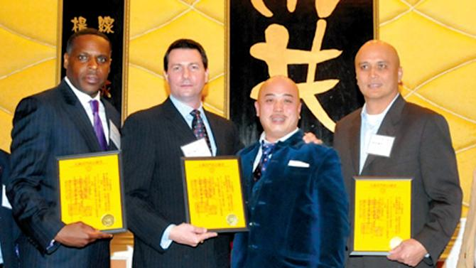 "FILE - In this file photo taken March 16, 2011, Raymond ""Shrimp Boy"" Chow, second from right, poses with several inducted consultants, including Keith Jackson, left, a former San Francisco school board member, at the Chee Kung Tong spring banquet in San Francisco. Jackson, who is playing a key role in the cash-for-guns political corruption investigation that has ensnared California state Sen. Leland Yee, appeared in federal court Thursday, April 3, 2014 for a bail hearing on charges that include bribery, drugs, guns and murder-for-hire conspiracy. Jackson was ordered released from jail pending trial. (AP Photo/Sing Tao Daily, File)"