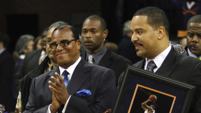 FILE - In this March 2, 2011, Nation of Islam Minister Louis Farrakhan, left, and his son Mustapha Farrakhan, are seen during ceremonies honoring Virginia seniors, including Mustapha's son, at an NCAA college basketball game in Charlottesville, Va.  A state law enforcement agency is investigating Mustapha Farrakhan after a newspaper determined he is a part-time suburban police officer who uses an unmarked squad car to provide traffic control for his father, an official said Monday April 22, 2013.   (AP Photo/Steve Helber, File)