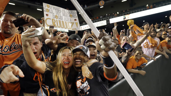 A fan takes a selfie with Baltimore Orioles center fielder Adam Jones after a baseball game against the Toronto Blue Jays, Tuesday, Sept. 16, 2014, in Baltimore. Baltimore won 8-2 to clinch the American League East. (AP Photo/Patrick Semansky)