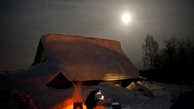 FILE - Musher Bill Pinkham collects hot water during his stop in Takotna, Alaska, during the Iditarod Trail Sled Dog Race on Wednesday night, March 7, 2012. (AP Photo/Anchorage Daily News, Marc Lester, File)