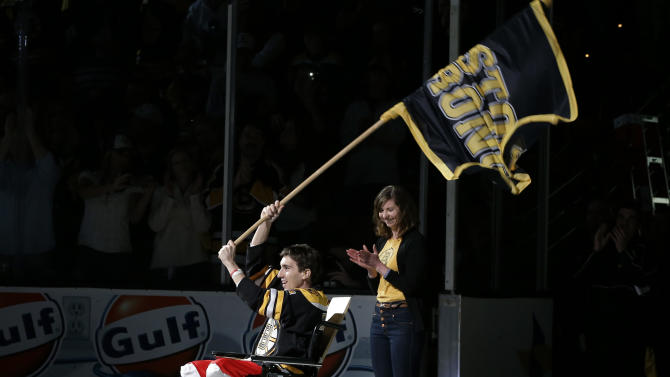 Boston Marathon bombing victim Jeff Bauman reacts as he is honored as the official flag-bearer before Game 2 of a first-round NHL hockey playoff series between the Boston Bruins and the Toronto Maple Leafs in Boston, Saturday, May 4, 2013. (AP Photo/Elise Amendola)