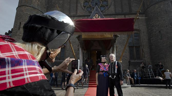"People in traditional Dutch clothes pose for pictures outside the 13th century ""Hall of Knights"", where Netherlands' King Willem-Alexander is to officially open the new parliamentary year with a speech outlining the government's plan and budget policies for the year ahead, in The Hague, Netherlands, Tuesday, Sept. 16, 2014. (AP Photo/Peter Dejong)"