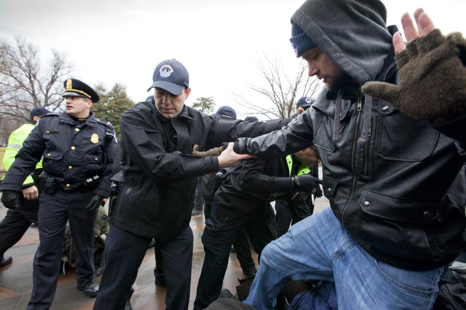 "A Capitol Hill Police officer assists a demonstrator as ""occupy Congress"" protesters are moved out of a restricted area on the West Lawn of the Capitol grounds in Washington, Tuesday, Jan. 17, 2012.  (AP Photo/J. Scott Applewhite)"