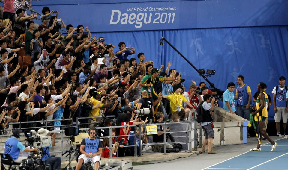 Spectators take photos of Jamaica's Usain Bolt, right bottom,  during a victory lap after winning the gold  in the Men's 200m final at the World Athletics Championships in Daegu, South Korea, Saturday, Sept. 3, 2011. (AP Photo/Shuji Kajiyama)