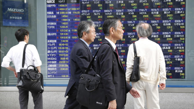 People walk by an electronic stock board of a securities firm as Japan's bench mark Nikkei 225 Index closed at 14,588.51 after gaining 119.37 points, or 0.83 percent, in Tokyo, Thursday, Oct. 17, 2013. An eleventh hour agreement that averted a U.S. government debt default boosted Asian stock markets Thursday. (AP Photo/Koji Sasahara)