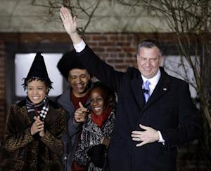 New York City Mayor-elect Bill de Blasio (R) waves while standing with his wife Chirlane McCray (2nd R), and children Dante and Chiara (L) after being sworn in as the mayor of New York City at the start of the new year, in New York January 1, 2014. REUTERS/Seth Wenig/Pool