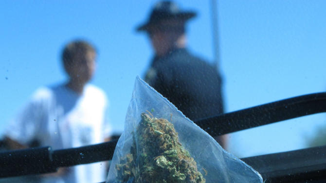 In this photo taken Wednesday June 20, 2012, David Kosmecki, left, talks to Idaho State Police Trooper Justin Klitch in Fruitland, Idaho. Kosmecki was stopped and charged with possession of marijuana after leaving Oregon.  As the Evergreen state works out the various complications of its new law,  including the fact that marijuana is still illegal under federal law, neighbors of Washington are watching with curiosity, and perhaps some apprehension. Idaho officials already have their hands full with Idahoans obtaining medical marijuana cards out of state. The Gem State borders three medical marijuana states, a reality that has caused medical marijuana arrests to outpace those of traffickers or other users. Although Idaho is a largely conservative state, there are pockets defined by borders and demographics that could create new challenges for law enforcement.  (AP Photo/Nigel Duara)