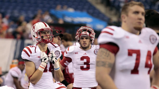 """FILE - This Dec. 1, 2012 file photo shows Nebraska quarterback Taylor Martinez (3) reacting on the sidelines with his teammates near the end of the Big Ten Conference championship NCAA college football game against Wisconsin in Indianapolis.  Nebraska offensive coordinator Tim Beck warns if the Cornhuskers have an emotional hangover from their 39-point Big Ten championship game loss, """"it's going to get ugly"""" when they play sixth-ranked Georgia in the Capital One Bowl. (AP Photo/Michael Conroy, File)"""