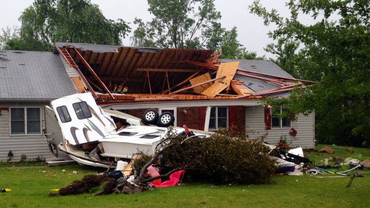 A camping trailer lies in the rear of a damaged home near Ronald Reagan Parkway in Plainfield, Ind., Tuesday, June 24, 2014. A tornado-producing storm hit central Indiana on Tuesday, damaging homes southwest of Indianapolis and downing power lines and uprooting trees in the city and its suburbs, authorities said. (AP Photo/The Indianapolis Star, Matt Kryger) NO SALES