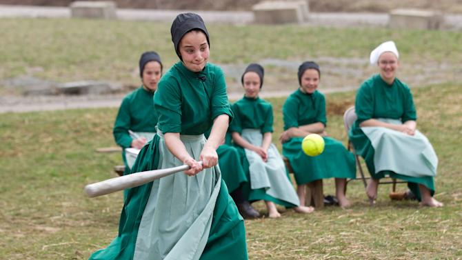 AP10ThingsToSee - Amish girls play softball after class during an end of the school year celebration in Bergholz, Ohio on Tuesday, April 9, 2013. The celebration was also part of a farewell picnic for four women and one man from this tight-knit group in rural eastern Ohio who will enter prison on Friday, April 12, 2013 joining nine already behind bars on hate crimes convictions for hair- and beard-cutting attacks against fellow Amish. (AP Photo/Scott R. Galvin, File)
