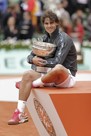 Rafael Nadal of Spain poses with the trophy after winning the mens final match against Novak Djokovic of Serbia at the French Open tennis tournament in Roland Garros stadium in Paris, Monday June 11, 2012. Rain suspended the final making it the first French Open not to end on Sunday since 1973. Nadal clinched his seventh title in four sets 6-4, 6-3, 2-6, 7-5, passing Sweden's Bjorn Borg as the all-time record-holder for French Open titles. (AP Photo/Bernat Armangue)