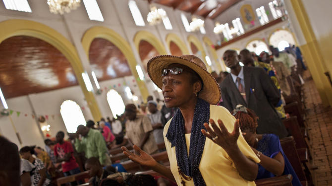A churchgoer raises her hands as she prays for peace in the New Year's Day morning mass at the Notre Dame Cathedral of the Immaculate Conception in Bangui, Central African Republic, Tuesday, Jan. 1, 2013. President Francois Bozize's government is coming under growing threat as rebels vowing to overthrow him rejected appeals from the African Union to hold their advance and try to form a coalition government. (AP Photo/Ben Curtis)
