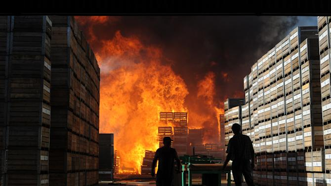 Farmers look on as around 18,000 empty fruit containers burn after being set alight by farm workers in Wolseley, South Africa, Wednesday, Nov. 14, 2012. Violent protests by farm workers have erupted in South Africa after weeks of unrest in the country's mining industry. Television images showed protesters overturn a police truck and set fires in the streets Wednesday in a town in South Africa's Western Cape. The workers have been protesting their wages, saying they want a minimum wage of $17 a day. Currently, workers make about half that amount a day. (AP Photo)