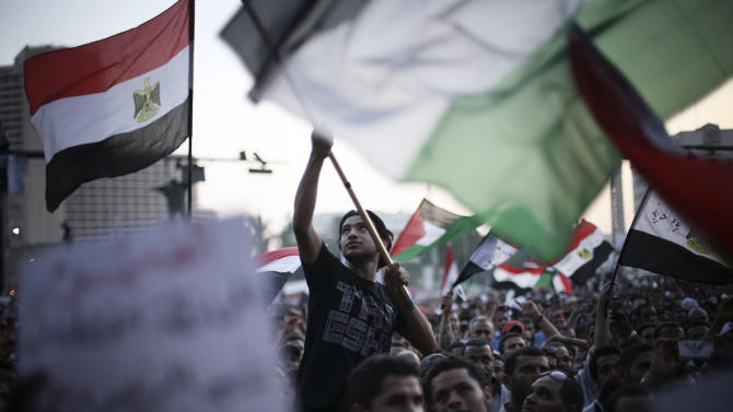 Egyptian protesters wave national flags and banners in Tahrir Square in Cairo, Egypt, Thursday, 21 June, 2012. Authorities delayed Thursday's planned announcement of the winner of Egypt's presidential election. Hundreds of Brotherhood supporters camped out in Cairo's Tahrir Square on Wednesday night, denouncing the ruling military and vowing to stay in place until the parliament, which was dissolved last week on a court order, is reinstated. (AP Photo/Manu Brabo)