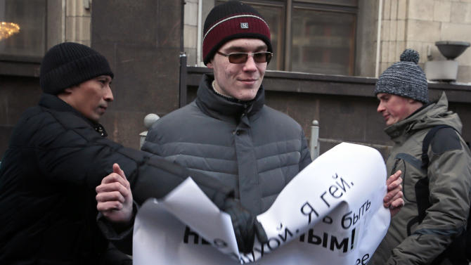 """A supporter of a bill banning """" homosexual propaganda"""" tries to grab a poster  from the hands of a gay rights activist, during a protest near the State Duma, Russia's lower parliament chamber, in Moscow, Russia, Friday, Jan. 25, 2013. A controversial bill banning """"homosexual propaganda"""" has been submitted to Russia's lower house of parliament for the first of three hearings on Friday, Jan. 25, 2013. The poster reads: I'm Blind and I'm Gay and I Refuse to be Invisible. P.S. Love is Stronger Then Hate.  (AP Photo/Mikhail Metzel)"""