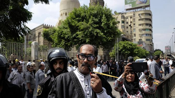 Egyptian security forces and civilians inspect the scene after a roadside bomb went off on a busy street in downtown near the foreign ministry, in Cairo, Egypt, Sunday, Sept. 21, 2014. Security officials said the Sunday explosion targeted a police checkpoint near the back gate of the ministry building. Several people were wounded, and senior policemen killed said the officials. (AP Photo/Aly Hazzaa, El Shorouk) EGYPT OUT