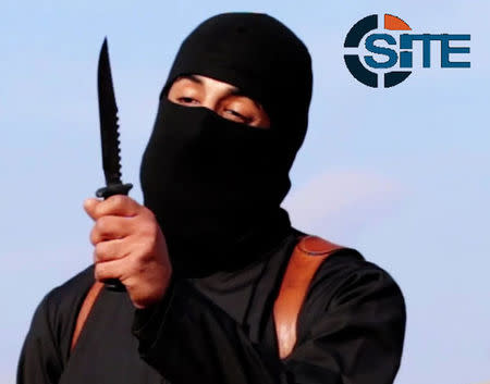A masked, black-clad militant brandishes a knife in this still image from video