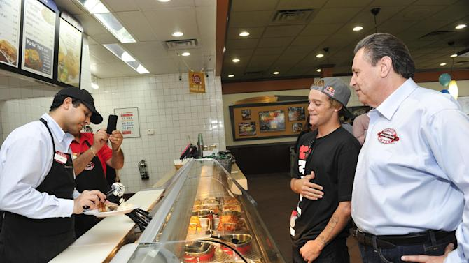 Boston Market CEO George Michel (A.K.A. The Big Chicken) and pro skateboarder Ryan Sheckler order lunch at Boston Market during an event benefiting The Sheckler Foundation on Thursday, Aug. 23, 2012 in North Arlington, N.J. (Photo by Charles Sykes/Invision for Boston Market/AP Images)